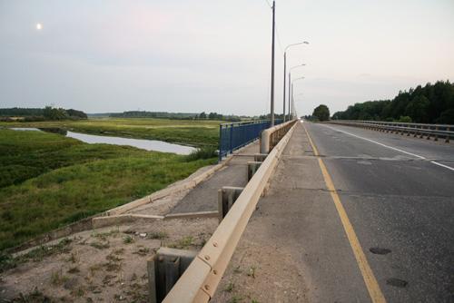 Для прохода на тротуар моста надо перелезать через отбойники